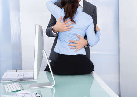 Businessman Embraces A Female Colleague Who Is Sitting Near A Desktop photo