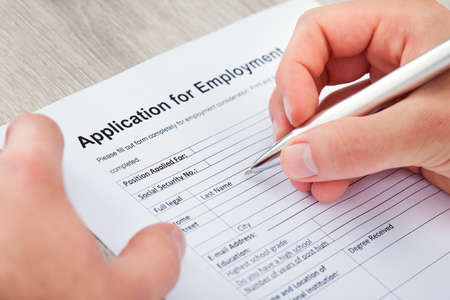 completing: Close-up Of Hand Filling Application For Employment