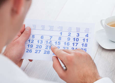 agenda: Close-up Of Man Marking With Pen And Looking At Date On Calendar