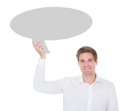 Portrait Of Young Man Holding Thought Bubble On White Background photo