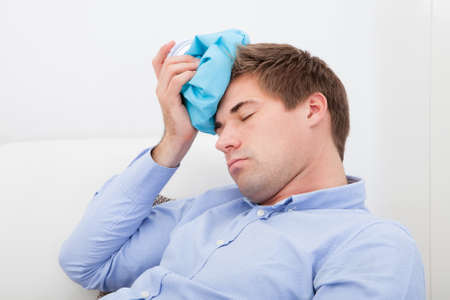 jaded: Young Man Suffering With Headache Applying Icepack