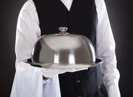 Portrait Of A Male Waiter Holding Tray And Lid Over Black Background photo
