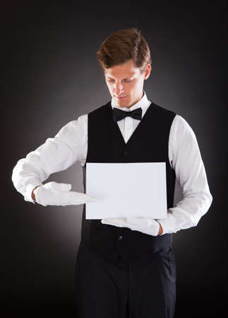 Young Waiter Presenting Blank Placard Over Black Background photo