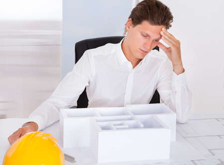 Frustrated Male Architect Sitting In Front Of Architectural Model In Office photo