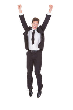 Excited Young Businessman With Arm Raised Standing On White Background photo