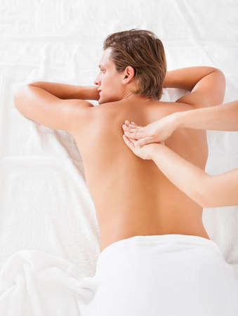 human back: Shirtless Man Lying On Front Getting Spa Treatment Stock Photo
