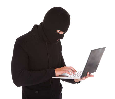 Portrait Of A Burglar Using Laptop Isolated On White Background photo