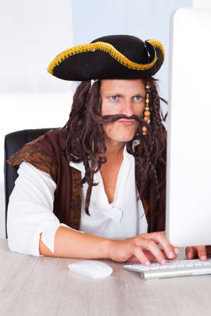Portrait Of A Young Pirate Using Computer At Desk photo
