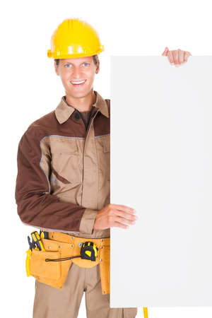 Mechanic Wearing Hardhat And Holding Blank Placard Isolated On White Background photo