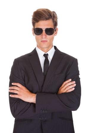 company secrets: Ritratto del maschio spia indossare occhiali da sole isolati su sfondo bianco