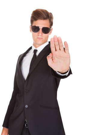 Portrait Of Male Guard In Suit Gesturing Stop Sign On White Background photo