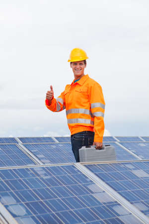 Happy Engineer With Toolkit Gesturing Thumb Up Sign photo