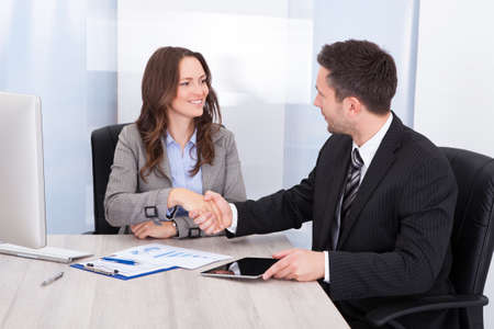transaction: Businesswoman Looking At Businessman While Shaking Hand At Office Desk