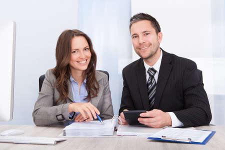 オフィスでの机に手形を計算する 2 つの若いビジネスマン 写真素材