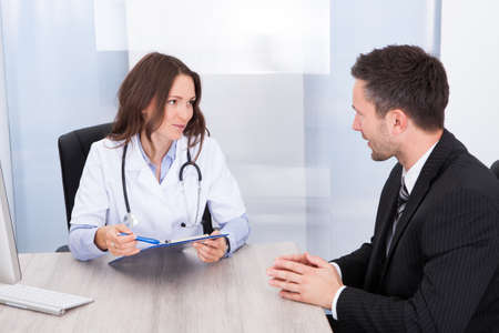 Young Female Doctor Holding Clipboard Talking With Businessman photo