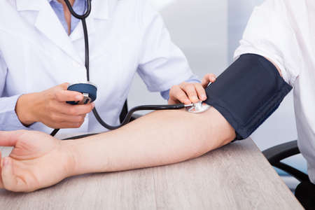 hypertension: Close-up Of Female Doctors Hand Checking Blood Pressure