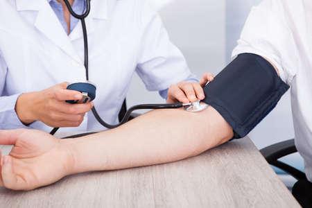 hipertension: Primer plano de la mano que controla la presión arterial del doctor de sexo femenino
