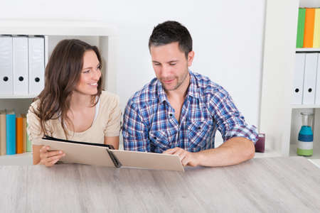 Portrait Of Happy Couple Sitting Side By Side Looking At Photo Album photo