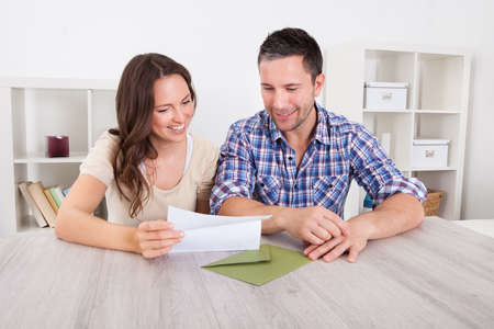 finance girl: Portrait Of A Happy Young Couple At Home Reading Paper Stock Photo
