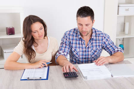 Portrait Of A Young Couple Calculating Finance At Desk photo
