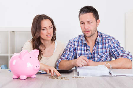 inserting: Young Man Looking At Woman Inserting Coin In Piggybank Stock Photo