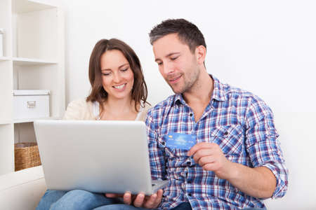 Portrait Of A Happy Young Couple Shopping Online With Credit Card photo