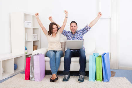 Excited Young Couple Sitting On Couch With Shopping Bag photo