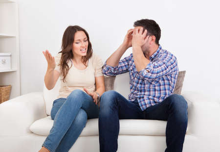 the opposite: Portrait Of Frustrated Couple Sitting On Couch Quarreling With Each Other
