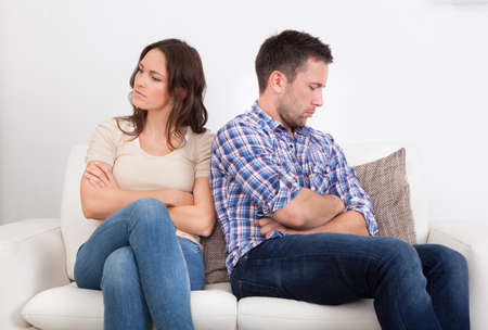 Displeased Couple Sitting Back To Back On Couch photo