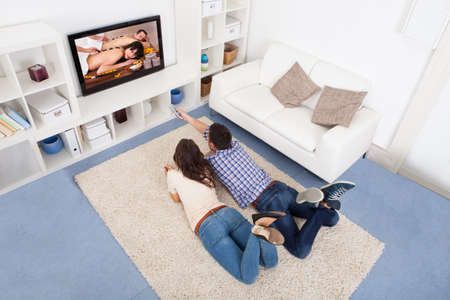 family sofa: Happy Young Couple In Livingroom Sitting On Couch Watching Television
