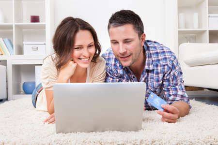 Happy Young Couple Shopping Online Using Laptop And Credit Card photo