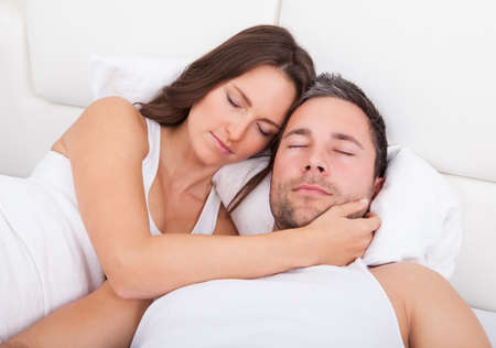 Young Couple Sleeping Side By Side On Bed photo