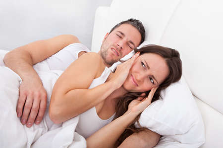 Frustrated Woman Disturbed With Man Snoring Behind Her photo
