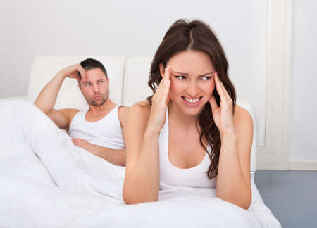 man and woman sex: Разочарованный женщина, сидя на кровати перед молодой человек