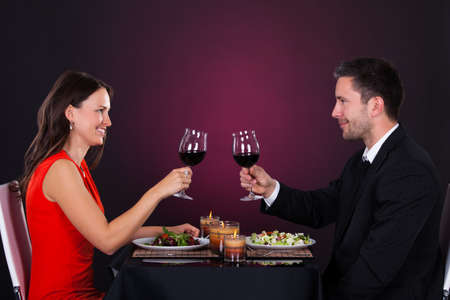 Smiling Couple Tossing Wine Glass While Having Dinner photo