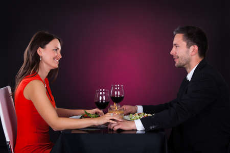 Young Smiling Couple Having Dinner With Wine Glass On Table photo