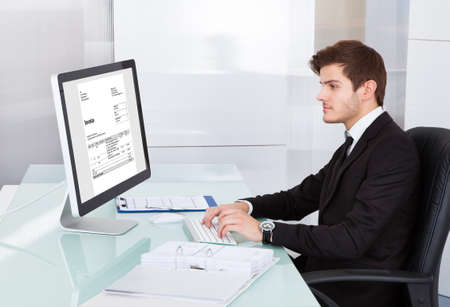 Portrait Of Young Businessman Using On Computer At Desk photo