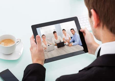 entrevista: Primer plano del hombre de negocios Mirando a la Conferencia de Video On Tableta digital