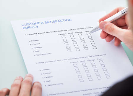 Close-up Of Man's Hand Filling Customer Survey Form photo
