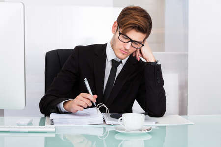 tired businessman: Portrait Of A Young Businessman Suffering From Headache In Office