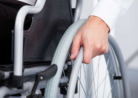 wheelchair: Close-up Of Businessman Sitting On Wheelchair In Office Stock Photo