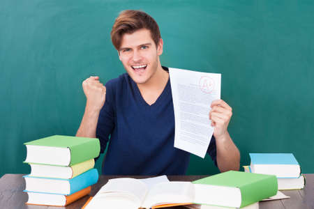 test paper: Portrait Of A Successful Student Holding Examination Paper