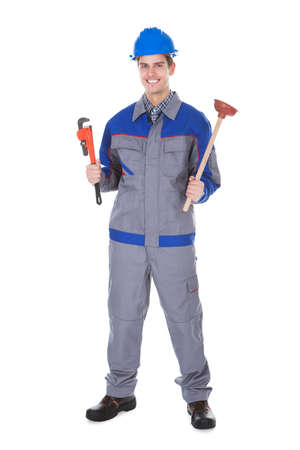 Portrait Of Male Worker Holding Wrench And Toolkit On White Background photo