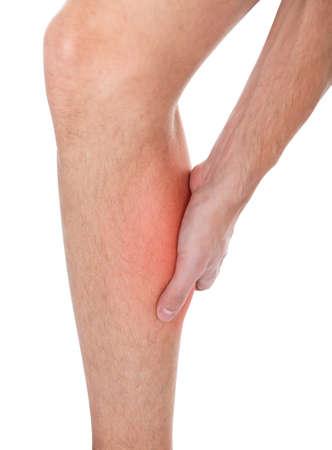 masaje deportivo: Primer plano de la pierna del hombre que sufre de lesiones en el fondo blanco