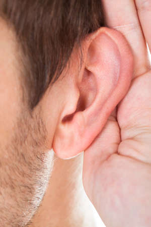 Close-up Of Person Trying To Hear With Hand Over Ear photo
