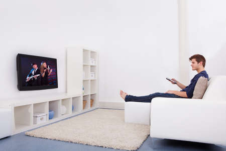 tv on wall: Young Man Sitting On Couch Watching Television