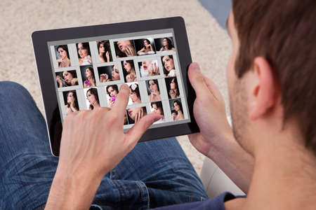 Close-up Of A Man Browsing Pictures Of Young Woman On Digital Tablet photo