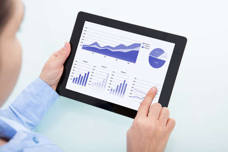 Close-up Of Businesswoman Analyzing Graph On Digital Tablet photo