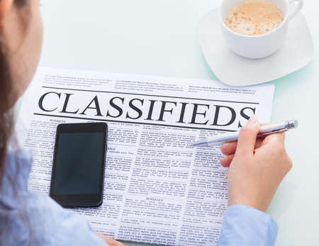 classifieds: Close-up Of A Businesswoman Holding Pen Reading Classifieds On Newspaper