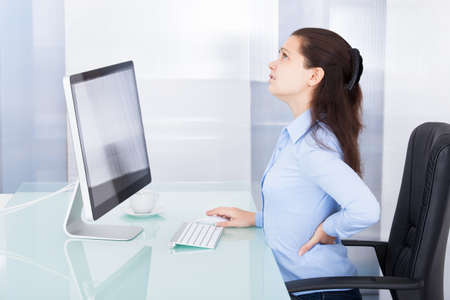 Portrait Of Young Businesswoman Suffering From Back Pain photo